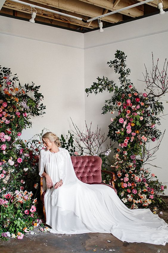 a luxurious floral photo booth with a dusty pink love seat and lush florals and greenery on both sides