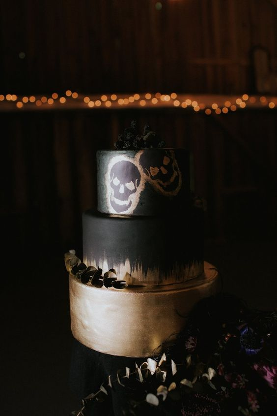 an impressive black and gold wedding cake with painted skulls topped with blackberries and eucalyptus