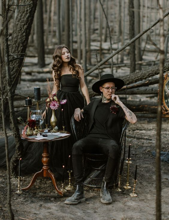 an offbeat look with a black tee, waistcoat, pants and boots plus a hat for a modern witch wedding