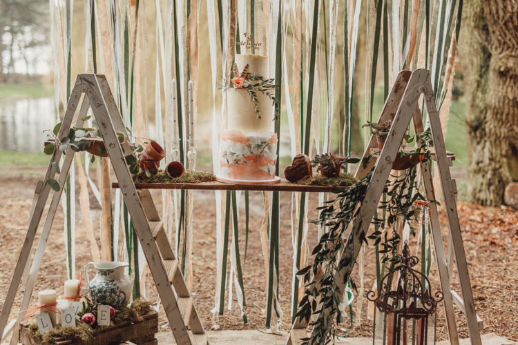 The wedding cake was displayed with using two ladders, moss and pots and candles