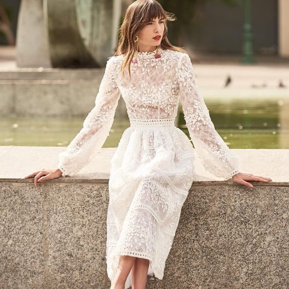 a lace and lace applique midi wedding dress with sleeves and an accented waist