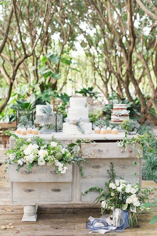 an outdoor dessert table decorated with greenery and blooms for an intimate garden wedding