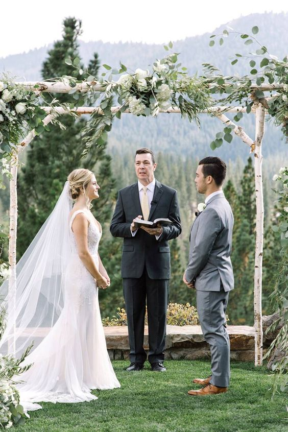 birch branch wedding arch topped with greenery and white blooms
