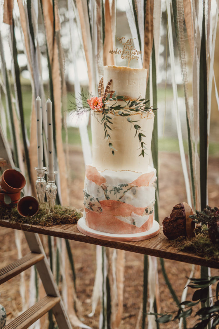 The cake was a semi naked one with greenery, feathers, blooms and a calligraphy topper