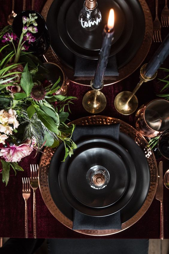 a Halloween table setting with a burgundy tablecloth, metallic hammered chargers, black candles and a chic floral centerpiece