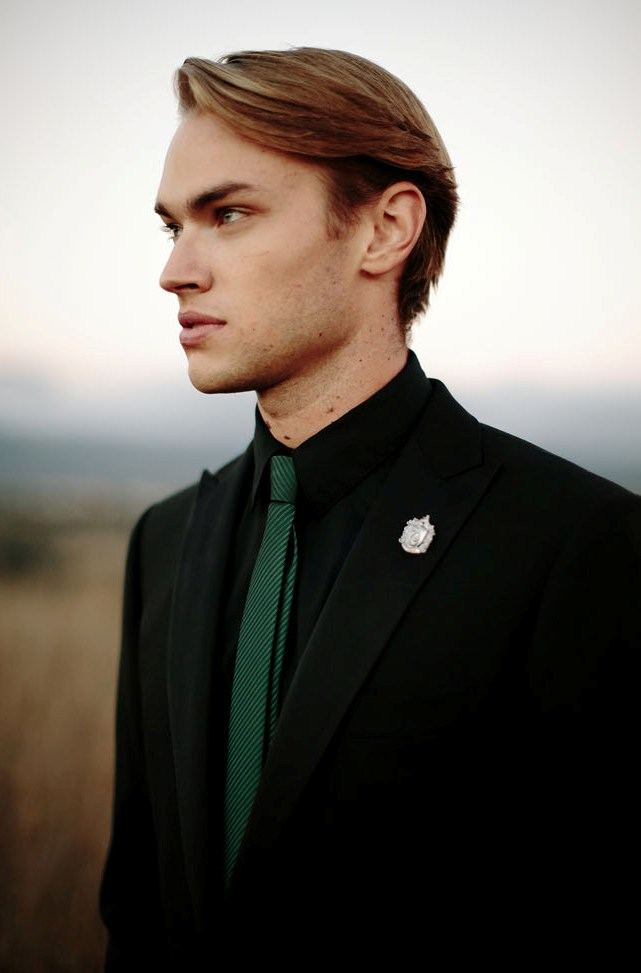 a black suit, a black shirt, an emerald tie and a silver badge instead of a boutonniere