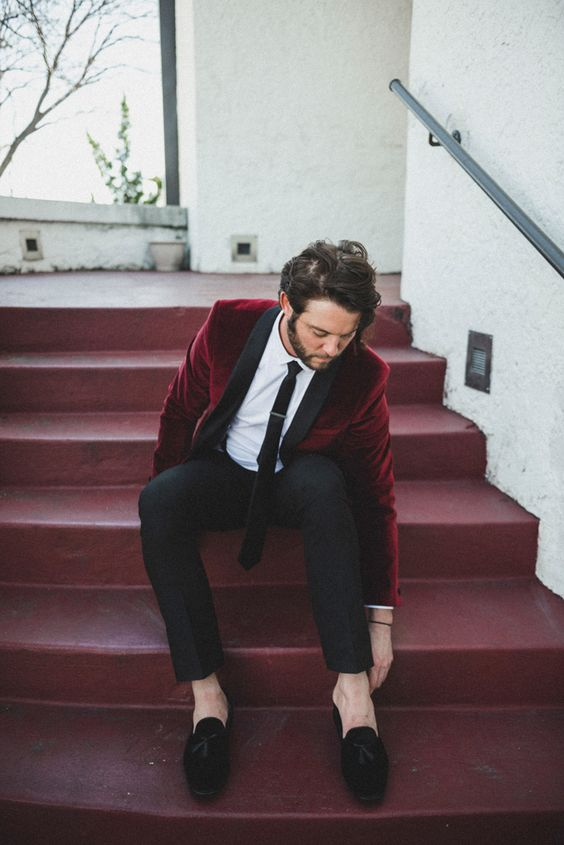 a chic groom's look with black pants and moccasins, a burgundy velvet blazer with black lapels and a black tie
