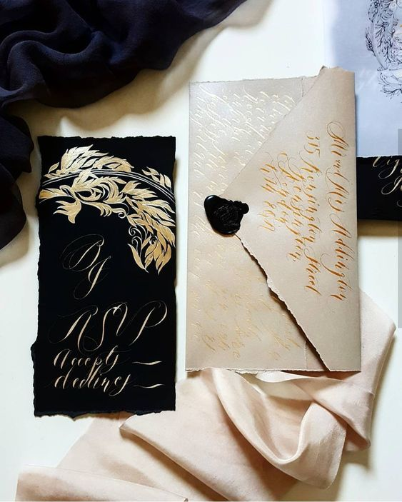 a luxurious wedding stationery set in off-white and black with gold calligraphy for a refined Halloween wedding