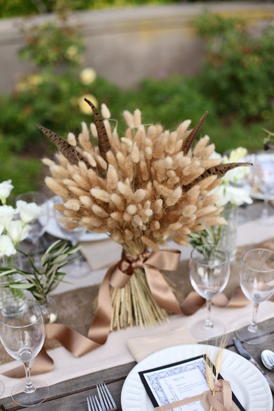 a traditional fall centerpiece of wheat and feathers and a silk brown ribbon