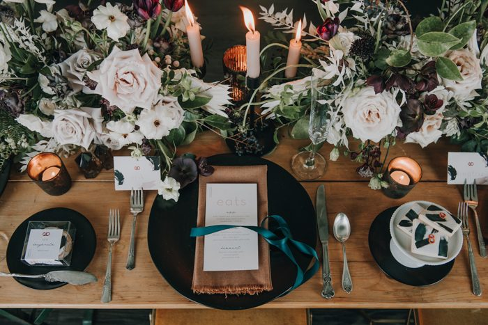 The wedding tablescape was done with matte black chargers, beige napkins and candles