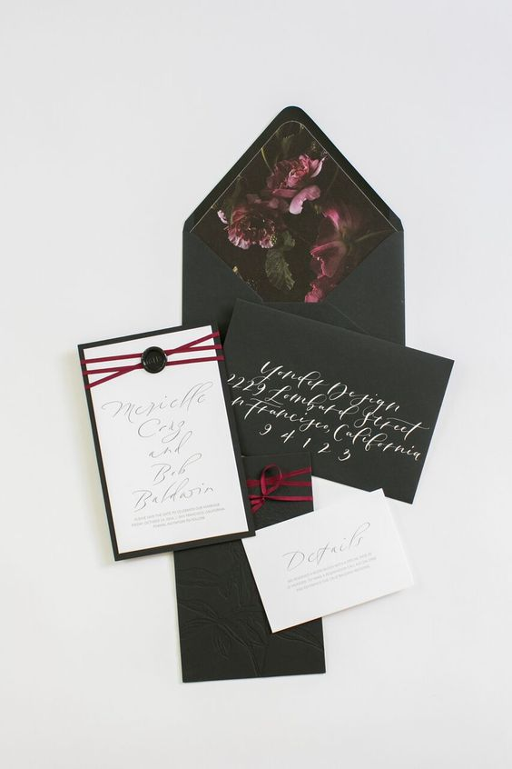 a moody invitation suite in black, white and plum, with dark floral lining and with plum ribbons