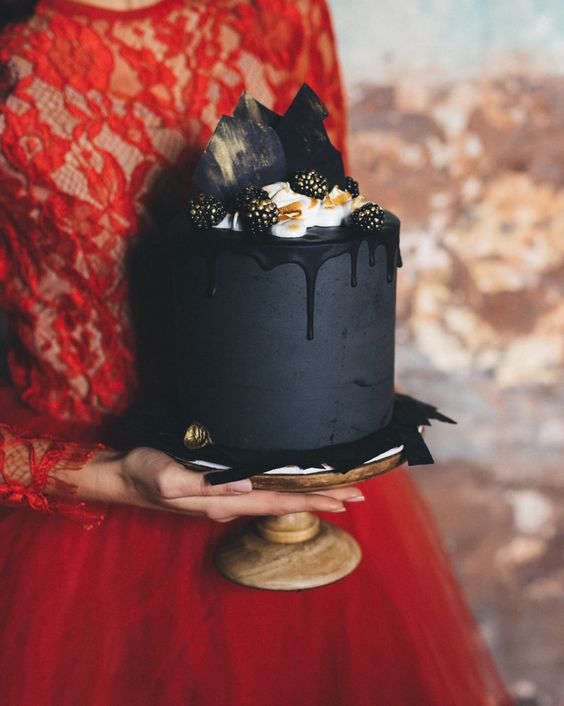 a moody matte black wedding cake with black drip, cream, gilded blackberries and black chocolate shards