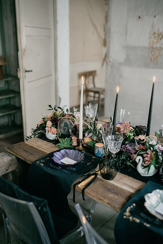 a moody wedding tablescape with black table runners and napkins, a textural floral table runner, black candles and puple plates