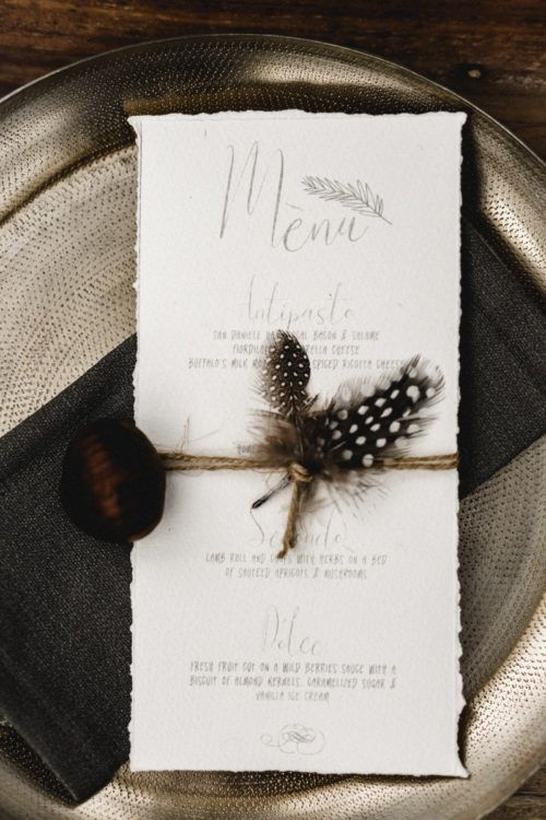 a wedding menu with twine, feathers and a nut attached for a fall boho wedding