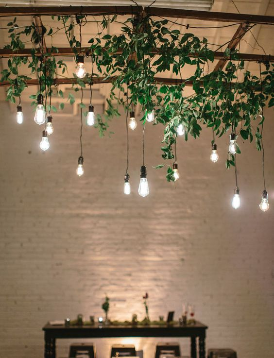 an overhead wedding decoration with greenery and hanging bulbs for an industrial feel