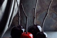 11 dark candied apples on branches are a bold and creative idea for Halloween favors or desserts