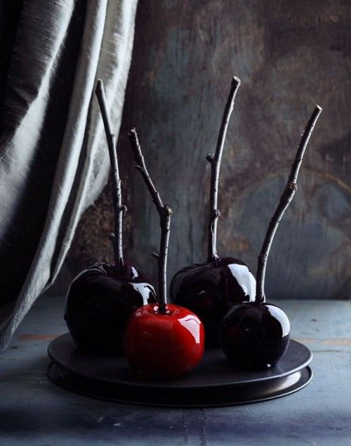 dark candied apples on branches are a bold and creative idea for Halloween favors or desserts
