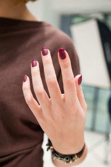 a bold fall take on the traditional FRench manicure, a matte burgundy nail and a shiny burgundy tip