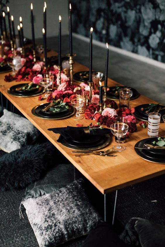 a chic moody tablescape with black plates and chargers, black candles, lush red and pink blooms right on the table