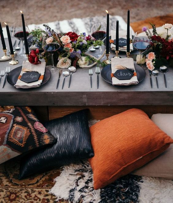 a chic wedding table setting with a low table, black chargers and candles, moody blooms and antlers plus feathers