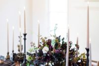 12 a moody centerpiece with a black bowl with greenery, dark foliage, purple and blush blooms and much texture