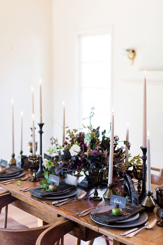 a moody centerpiece with a black bowl with greenery, dark foliage, purple and blush blooms and much texture
