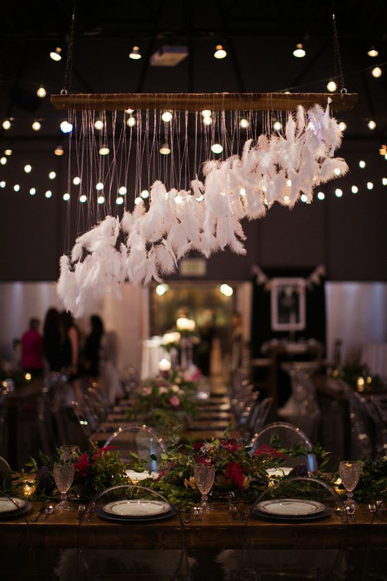 an airy feather hanging over the sweetheart table is a great touch to a boho reception