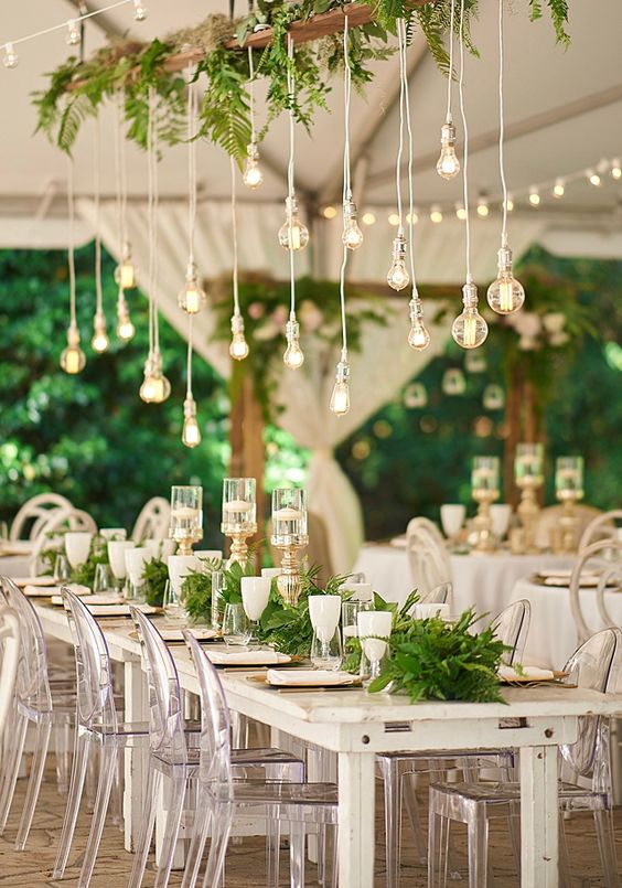 an overhead wedding decoration with cascading ferns and some bulbs hangign down