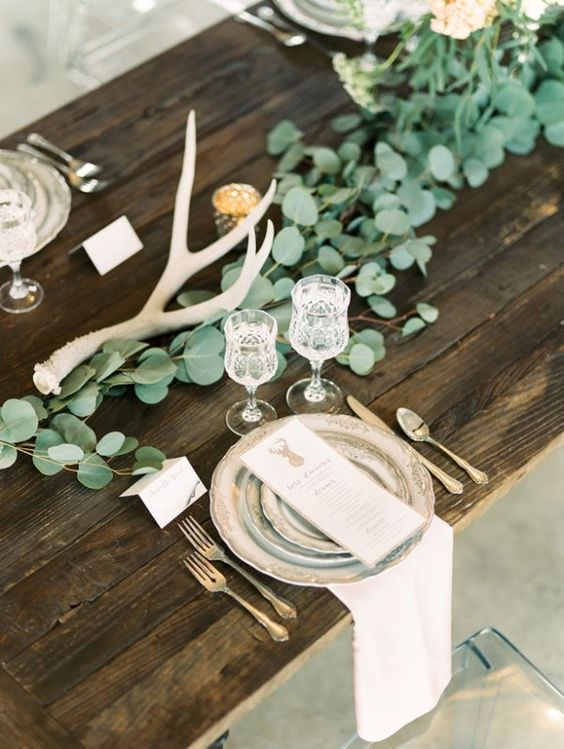fresh eucalyptus and antlers plus an uncovered table are right what you need for a mountain wedding