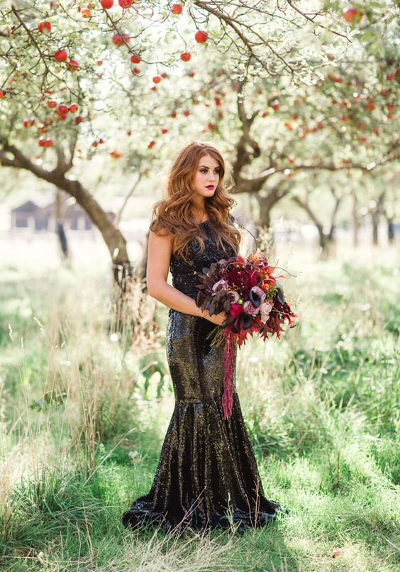 a black sequin mermaid wedding dress with a lace bodice and a burgundy and black wedding bouquet
