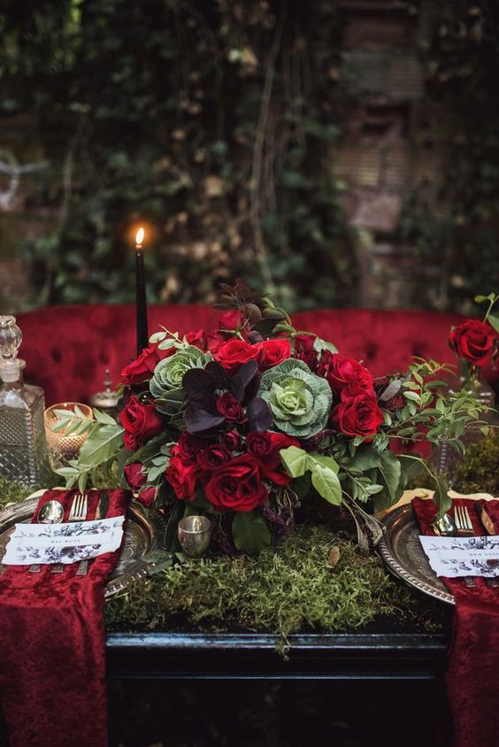 a dark romance tablescape with a moss table runner, red napkins, black candles and a lush wedding centerpiece with veggies