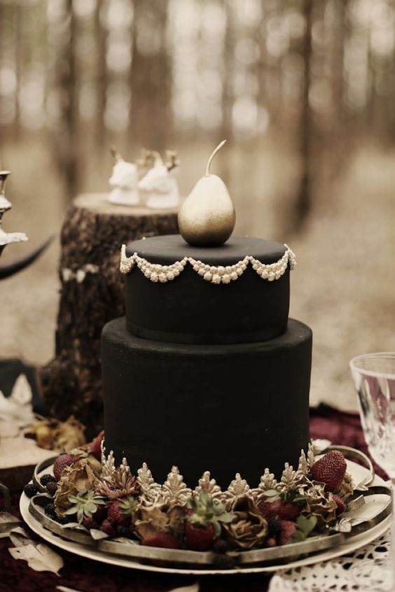 a haunted black wedding cake with white touches, berries on the bottom and a silver pear on the top