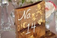 13 a rustic wooden table number with calligraphy and gold foil touches
