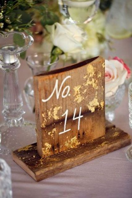 a rustic wooden table number with calligraphy and gold foil touches