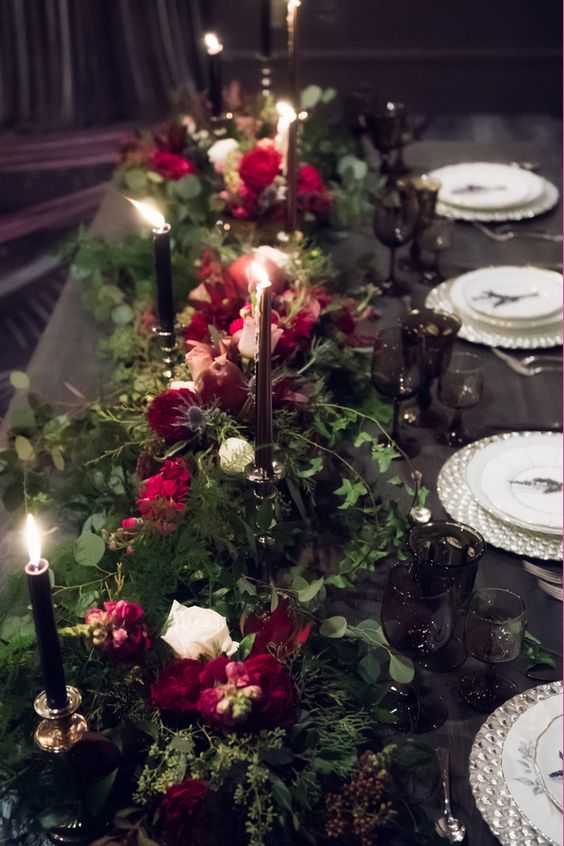 a table lined up with lush greenery, burgundy and white blooms and black candles