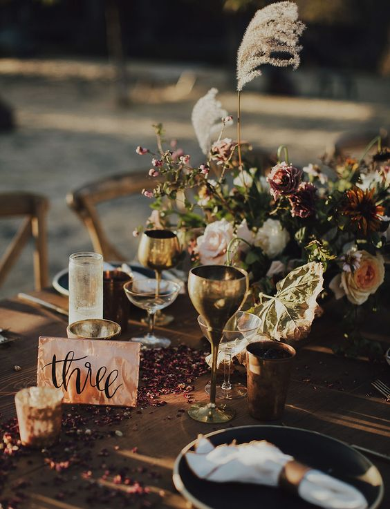 moody boho touches - dusty-colored blooms, herbs and some petals on the table for a boho mountain wedding
