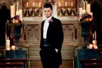 14 a black suit with a dinner jacket, a thick sash, black shoes and a pink rose boutonniere for a Gothic groom's look