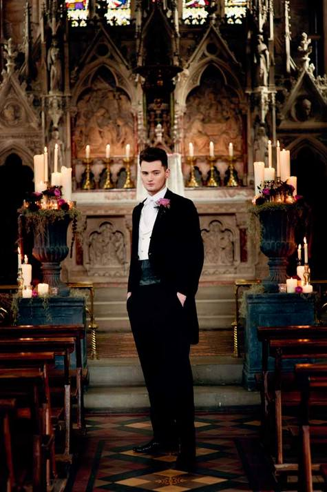 a black suit with a dinner jacket, a thick sash, black shoes and a pink rose boutonniere for a Gothic groom's look