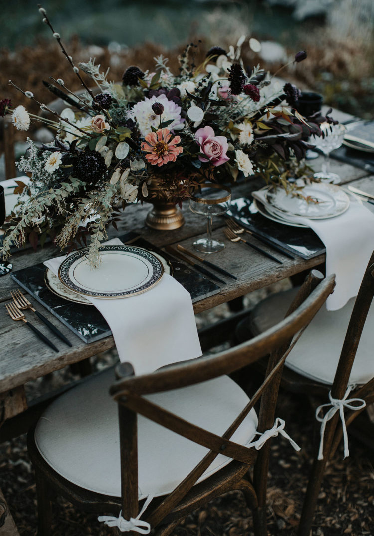 a gorgeous haunted tablescape with a lush textural centerpiece, marble chargers, printed plates, gilded touches and white napkins