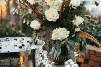 14 a gorgeous wedding centerpiece with feathers, moss, greenery, white blooms and greenery