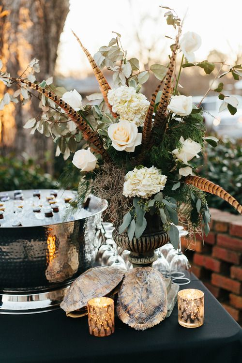 a gorgeous wedding centerpiece with feathers, moss, greenery, white blooms and greenery