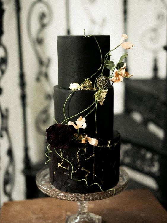 a refined black wedding cake with two matte tiers and a textural tier with gold touches, topped with flowers and herbs
