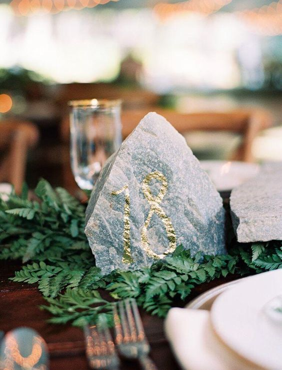 a rock table number with gold foil is a cool idea for a mountain wedding