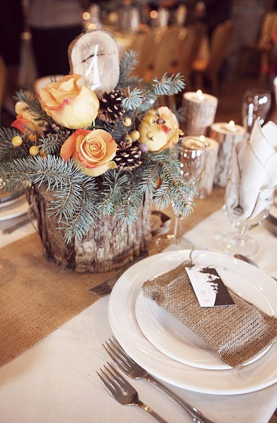 a rustic centerpiece with wood slices, evergreens, pinecones and orange roses for a winter mountain wedding