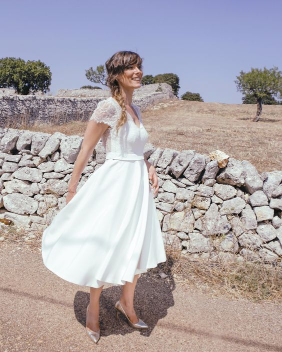 a chic midi wedding gown with a lace bodice with short sleeves and a V-neckline and a plain skirt plus metallic shoes
