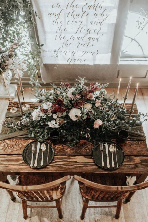 a haunted table setting with a lush floral centerpiece, off-white candles, black cahrgers and a grey table runner