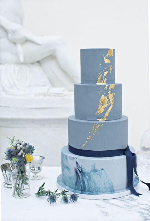 a blue wedding cake with a marble tier and touches of gold foil for a coastal wedding