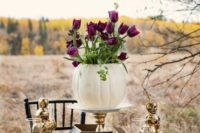 16 a centerpiece composed of a white pumpkin vase with purple tulips and gilded skull towers