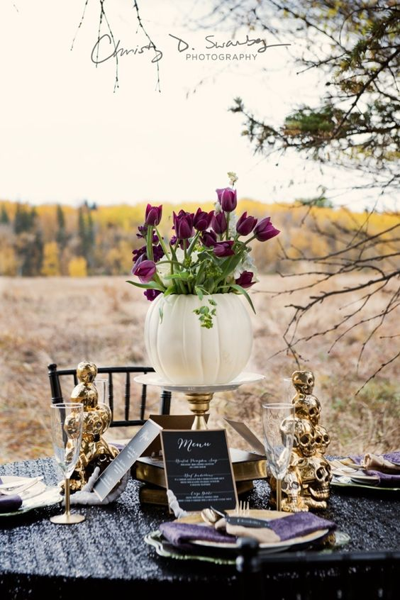 a centerpiece composed of a white pumpkin vase with purple tulips and gilded skull towers