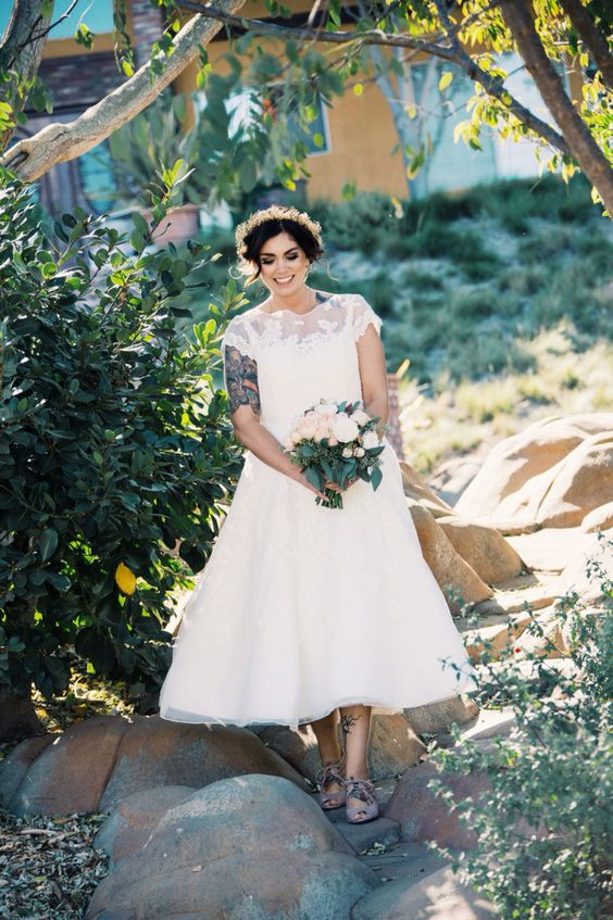a chic vintage inspired tea length lace wedding dress with an illusion neckline and grey strappy shoes